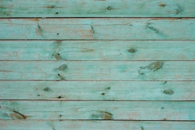 緑のペンキの残骸が付いている古い板の質感