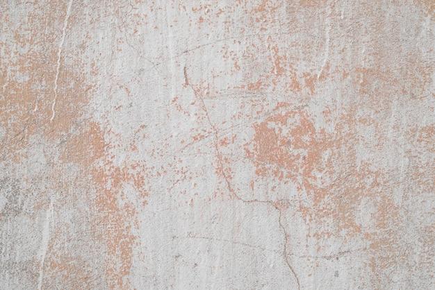 外の古いコンクリート壁のテクスチャ、クローズアップ。赤いペンキの色あせ、傷、損傷。