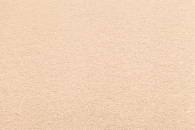 Текстура старой светлой бежевой бумажной предпосылки.