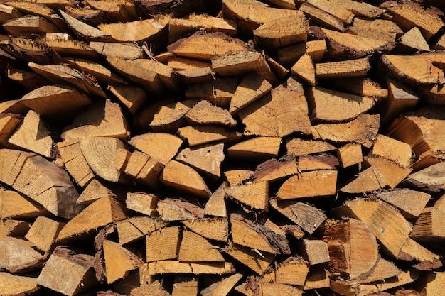 松の薪のテクスチャ。薪が欠けている。薪のウッドパイルのクローズアップ。乾いた薪、目に見える質感、木の亀裂。セレクティブフォーカス。