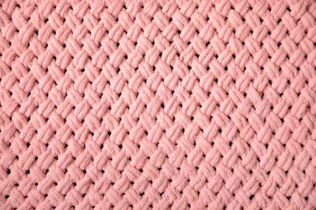 핑크 빅 니트 담요의 질감. 큰 뜨개질 격자 무늬