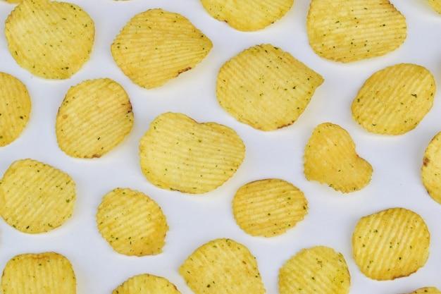 Текстура картофельных чипсов на светлом фоне, вид сверху. концепция вредного питания