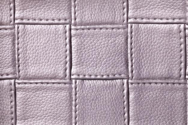 Текстура фиолетовой кожи с квадратным узором и строчкой