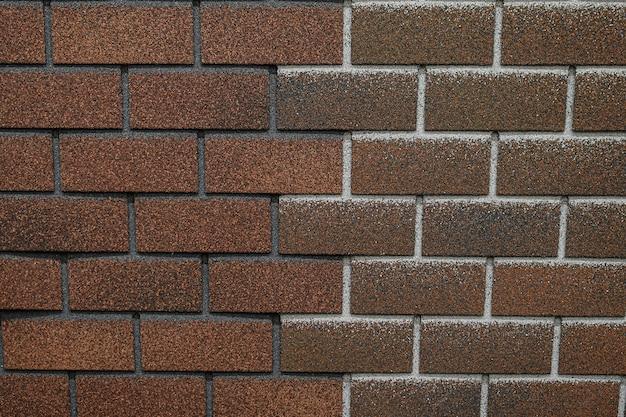 れんが造りの形の帯状疱疹のテクスチャ。信頼性の高い瀝青屋根材。家の屋根を覆うための建築材料。屋根瓦は茶色で、白と黒の静脈があります。クローズアップ、粒子の粗い表面