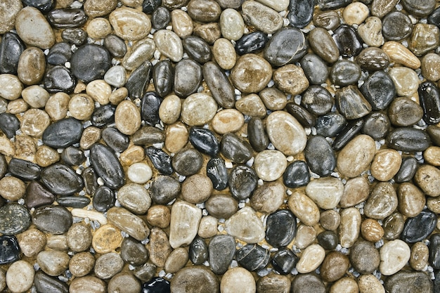 Фактура из гладких камней, декоративно выложенных на земле фрагмент ландшафтного дизайна