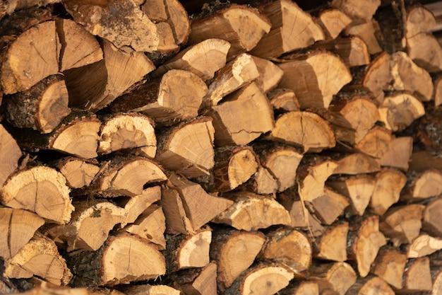 ウッドパイルに積み上げられたみじん切りのオーク薪の背景画像のテクスチャ。スペースをコピーします。セレクティブフォーカス。