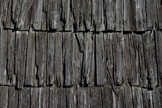 집의 오래 된 나무 지붕의 질감입니다. 전통적인 농촌 건축의 세부 사항