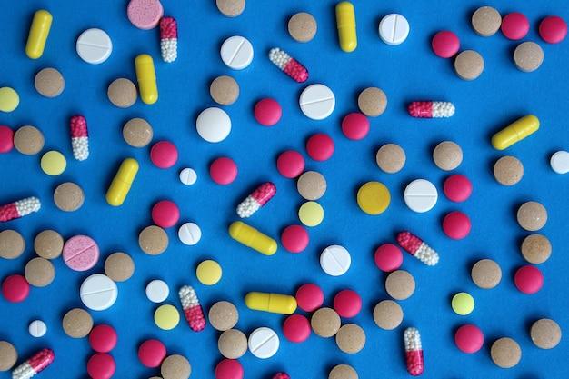 青い壁に散らばっている様々な薬や錠剤の質感。明るくマルチカラーのピル。健康と医学のテーマ。