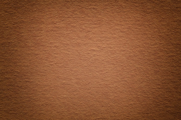 Текстура старинного темного бронзового бумажного фона с виньеткой. структура плотного светло-коричневого крафт-картона с рамкой. войлок ржавый градиент фона крупным планом.