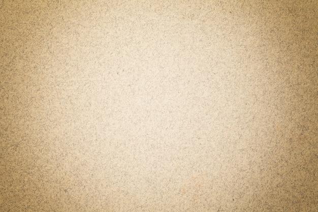 Текстура винтажной русой бумажной предпосылки с матовой виньеткой. структура бежевого крафт-картона с рамкой.