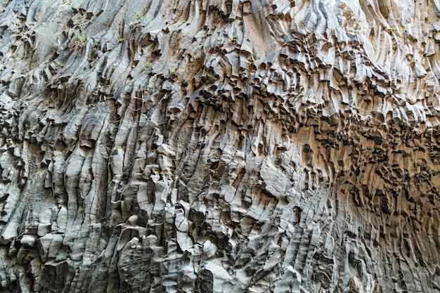 Текстура вулканического камня. каменные склоны ущелья алькантара образованы лавой вулкана этна, остров сицилия в италии.