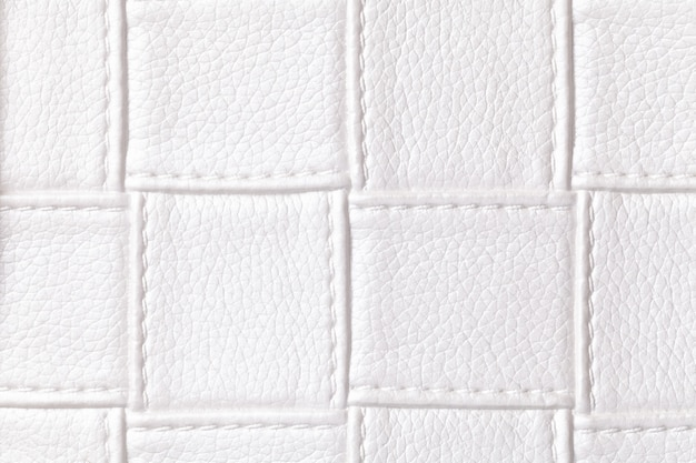 正方形のパターンとステッチ、マクロと白い革の背景のテクスチャ。幾何学的形状のテキスタイルからの要約。