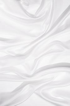 Текстура белой шелковой ткани, текстильный фон, драпировка и складки на нежной ткани. жесткий свет и вид сверху.