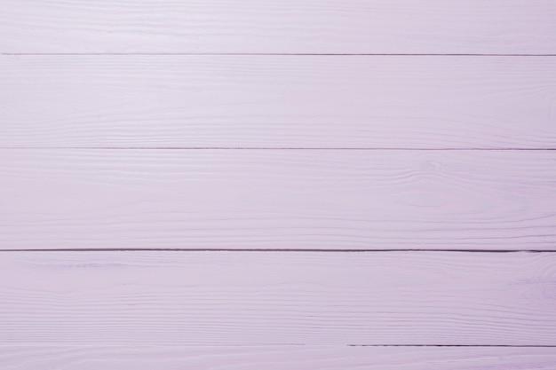 クローズアップによる淡いピンク色の木製の背景の質感。