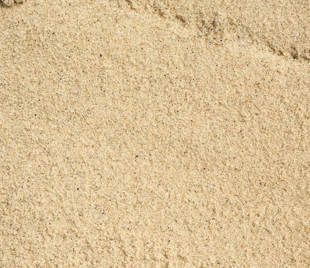 Текстура желтого песка на черном море, вид сверху