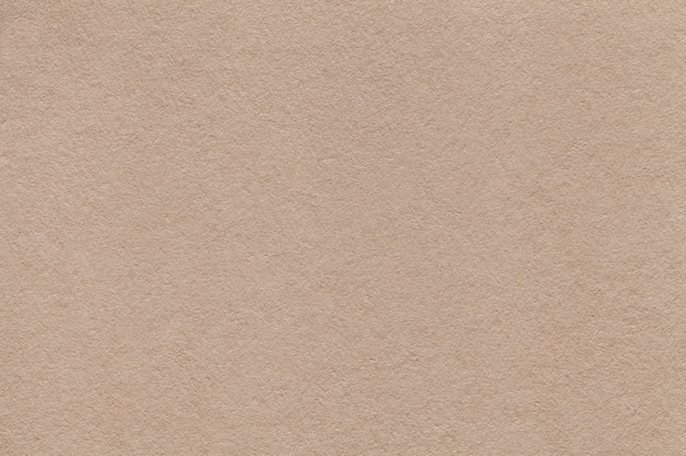 Texture of old beige paper closeup. structure of a dense cardboard sand color. the background.