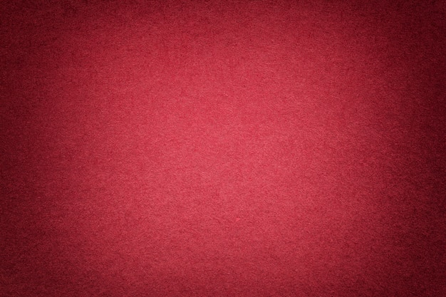 Texture of old bright red paper background, closeup. structure of dense cardboard.