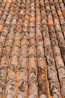 The texture of the old brown shingles on the roof of the building
