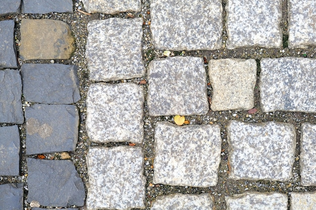 Texture of old cobbled pavement close-up. granite stone background.