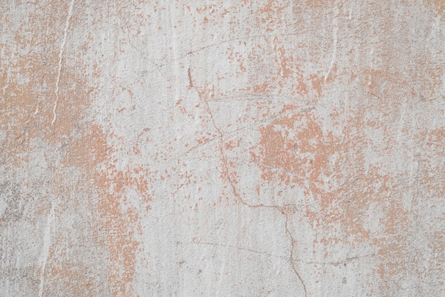 Texture of old concrete wall outside, close-up. faded red paint, scratches, damage.