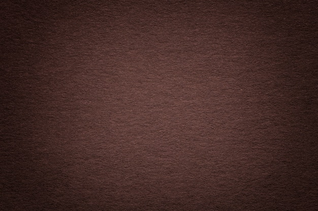 Texture of old dark brown paper background, closeup. structure of dense beige cardboard.