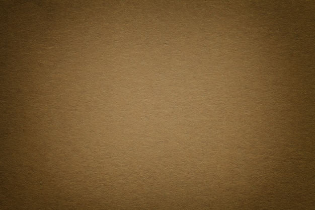 Texture of old dark brown paper background, closeup. structure of dense cardboard.