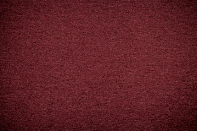 Texture of old dark red paper background, closeup