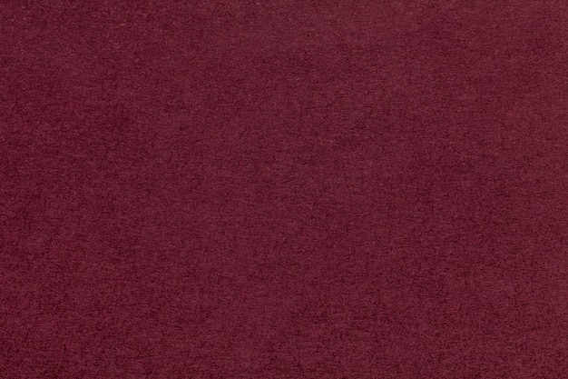 Texture of old dark red paper closeup. structure of a dense cardboard. the maroon background.