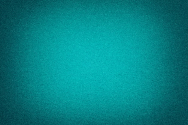 Texture of old dark turquoise paper background, closeup. structure of dense emerald cardboard.