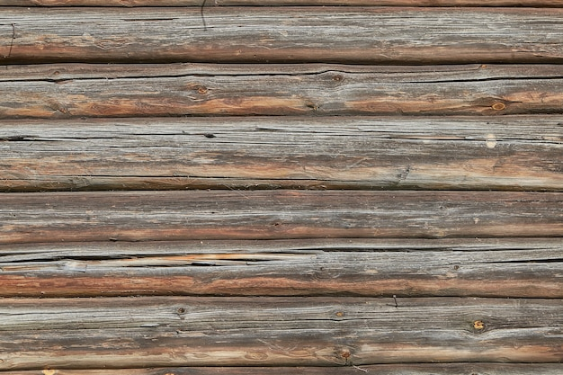 Texture of an old faded log wall with cracks.