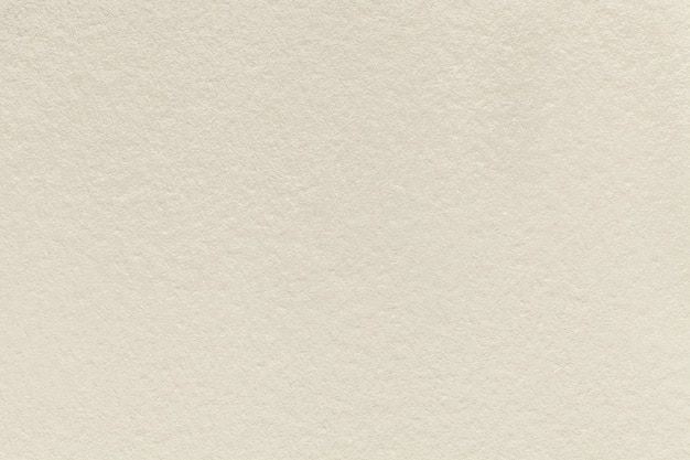 Texture of old light beige paper background of dense sand cardboard
