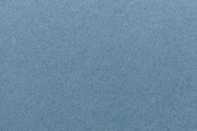 Texture of old light blue paper closeup. structure of a matte dense cardboard wallpaper. denim felt background