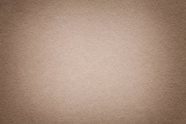 Texture of old light brown paper background, closeup. structure of dense beige cardboard.