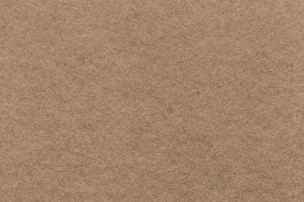 Texture of old light brown paper background, closeup. structure of dense cardboard
