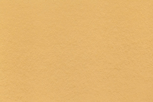 Texture of old light yellow paper closeup. structure of a dense cardboard. the golden background
