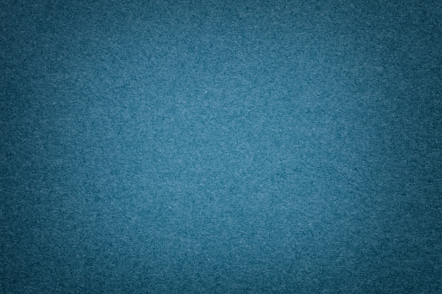 Texture of old navy blue paper background, closeup. structure of dense denim cardboard.