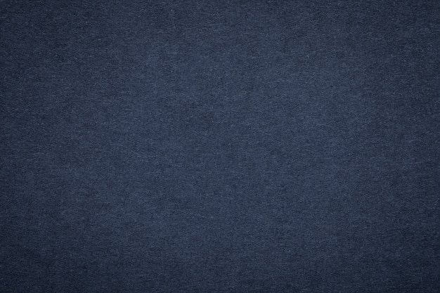 Texture of old navy blue paper, closeup. structure of dense dark denim cardboard