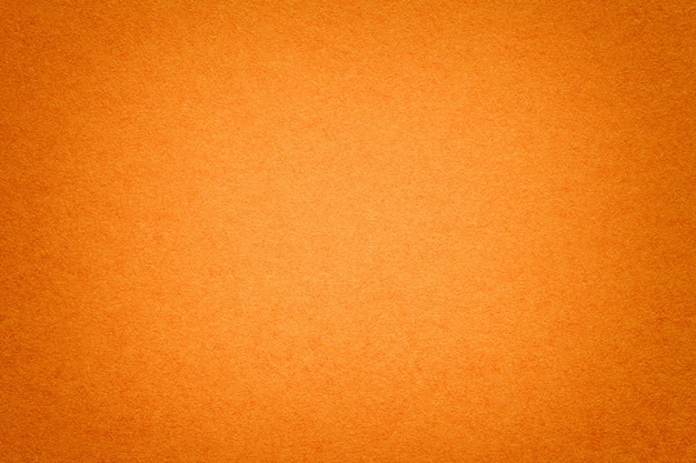 Texture of old orange paper background, closeup. structure of dense cardboard.