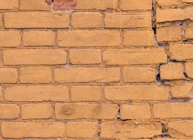 Texture of old painted yellow brick of color
