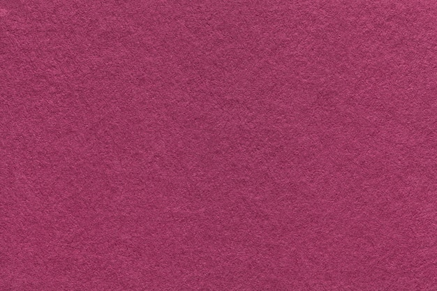 Texture of old purple paper background, closeup. structure of dense magenta cardboard