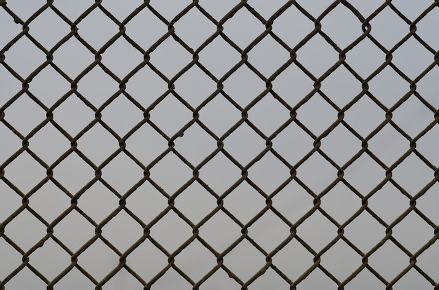 Texture of an old and rusty metal mesh on a neutral background