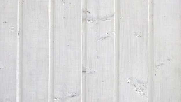 Texture of old wood planks with peeling white paint