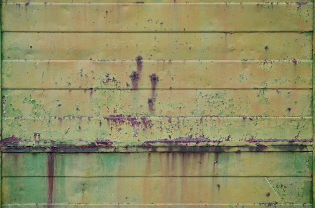 Texture of an old yellow metal wall with significant damage from exposure to unfavorable weather conditions and dampness
