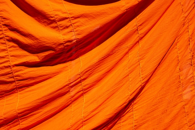 Texture of orange robe of a buddhist monk or novice for background