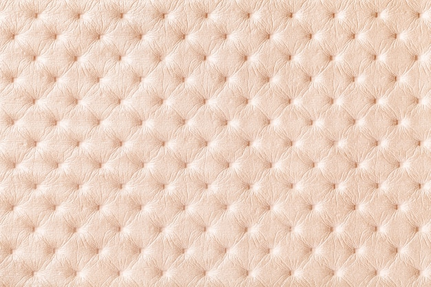 Texture of pearl beige leather fabric background with capitonner style. cream textile of chesterfield style.