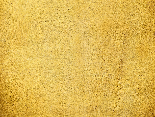 Texture of plastered old wall with cracks painted in yellow. empty grunge background