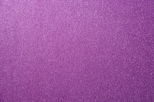 Texture of purple glitter paper background for design christmas or new year's cards