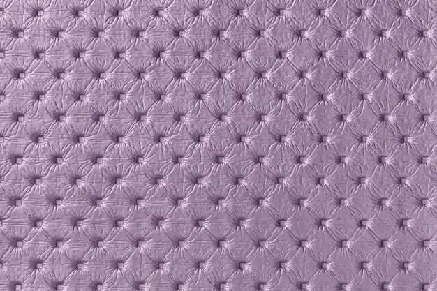 Texture of purple leather fabric background with capitone pattern, macro. violet textile of chesterfield style.