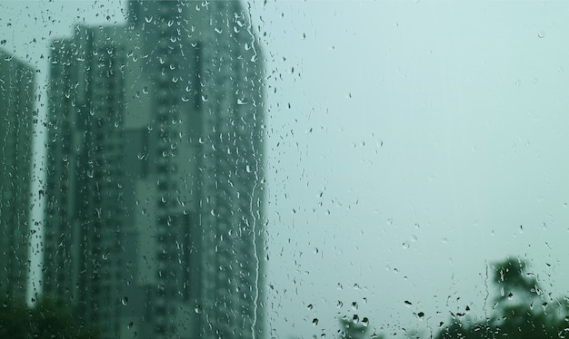 Texture of rain drops on window glass with blurry skyscrapers and overcast sky in background