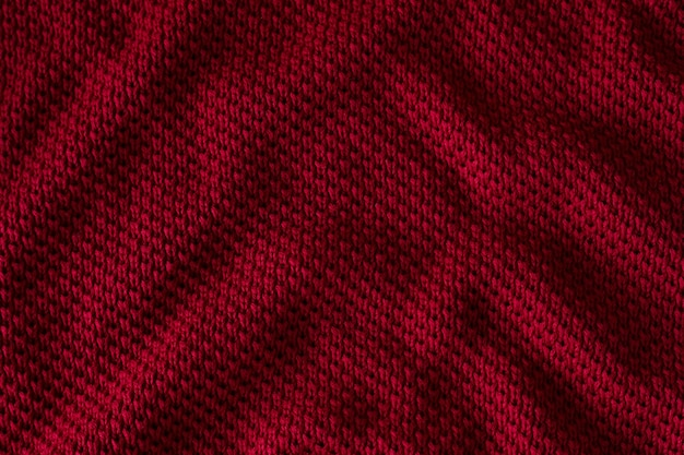 Texture of red knitted sweater closeup burgundy background